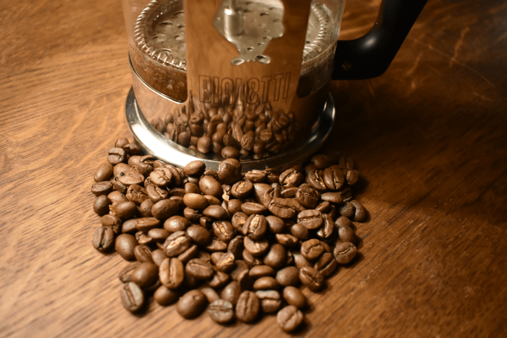 French press with coffee beans in front