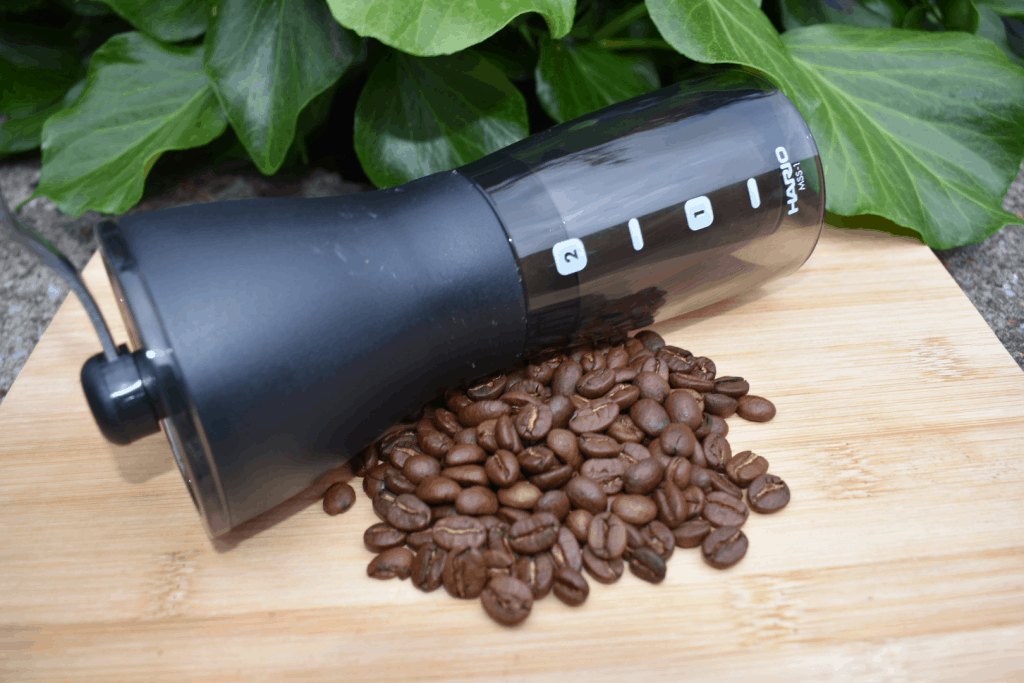 Hand coffee grinder with coffee beans in front