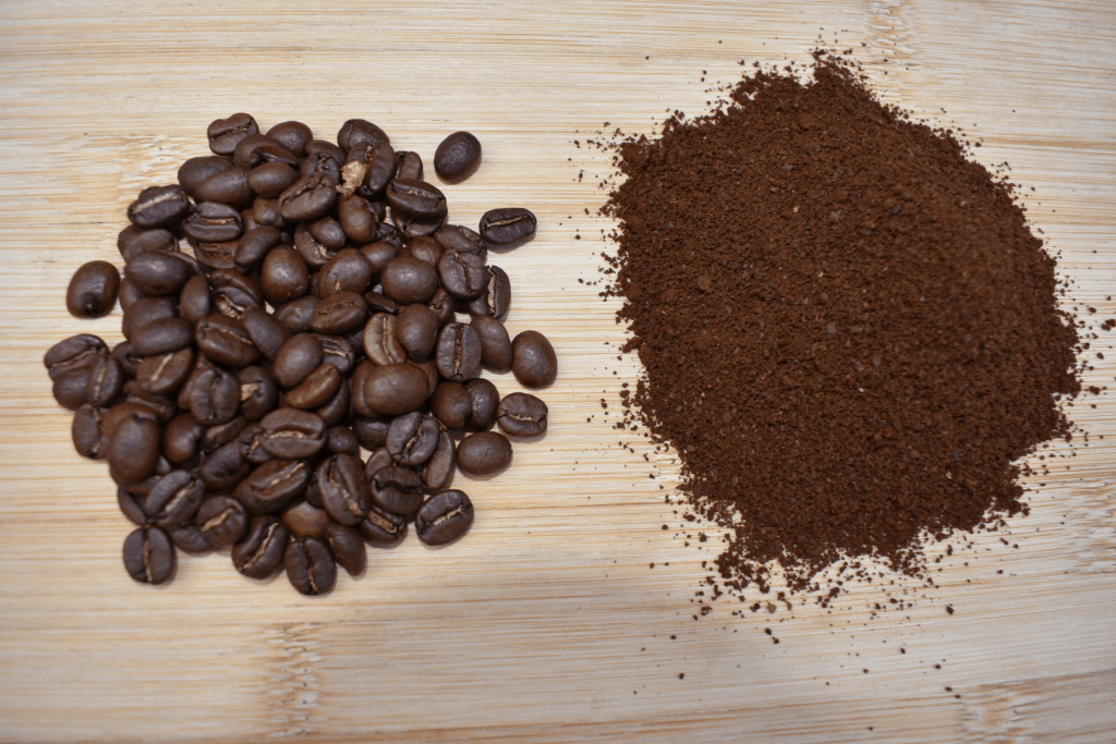 Whole coffee beans compared to ground coffee