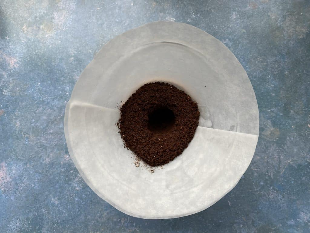 """""""Ground coffee is added into the coffee filter of the Chemex"""""""