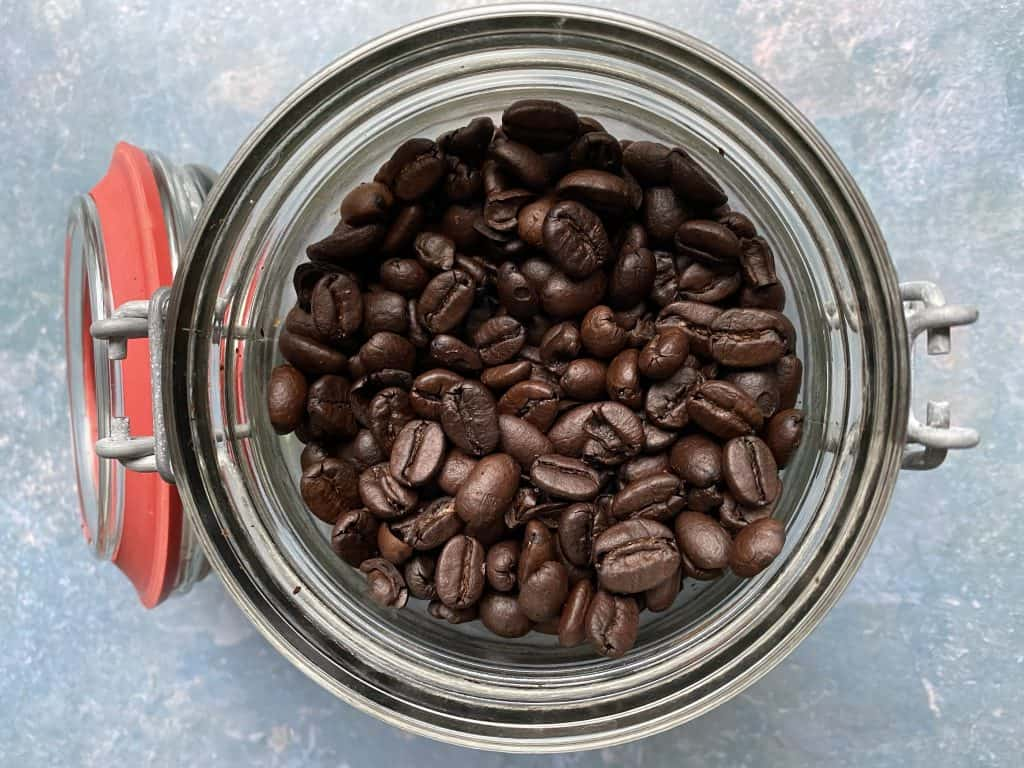 """Dark roasted coffee beans in a jar"""