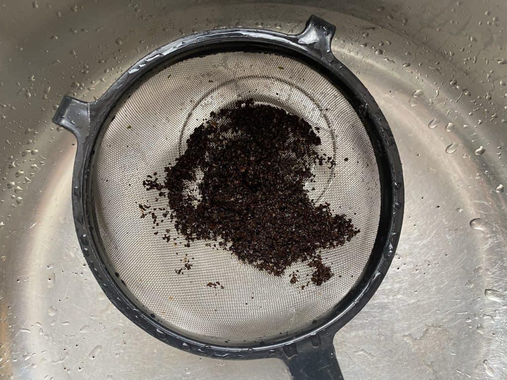 """Ground coffee beans in mesh sieve"""