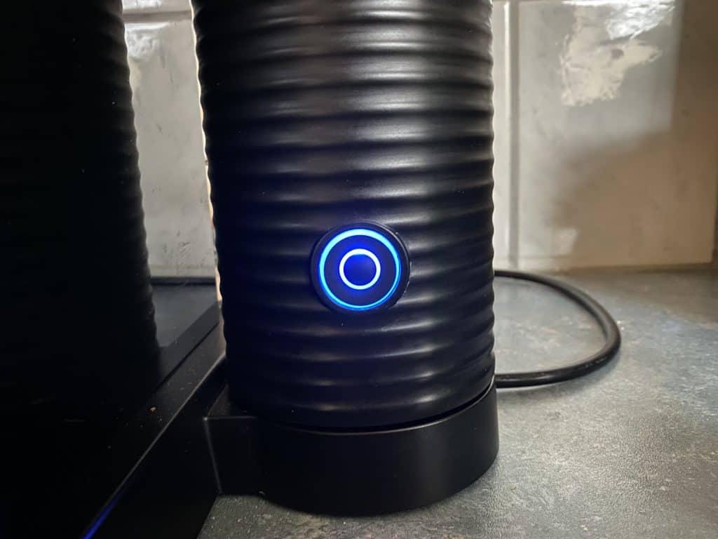 """Blue button lighting up on the Aerocinno"""