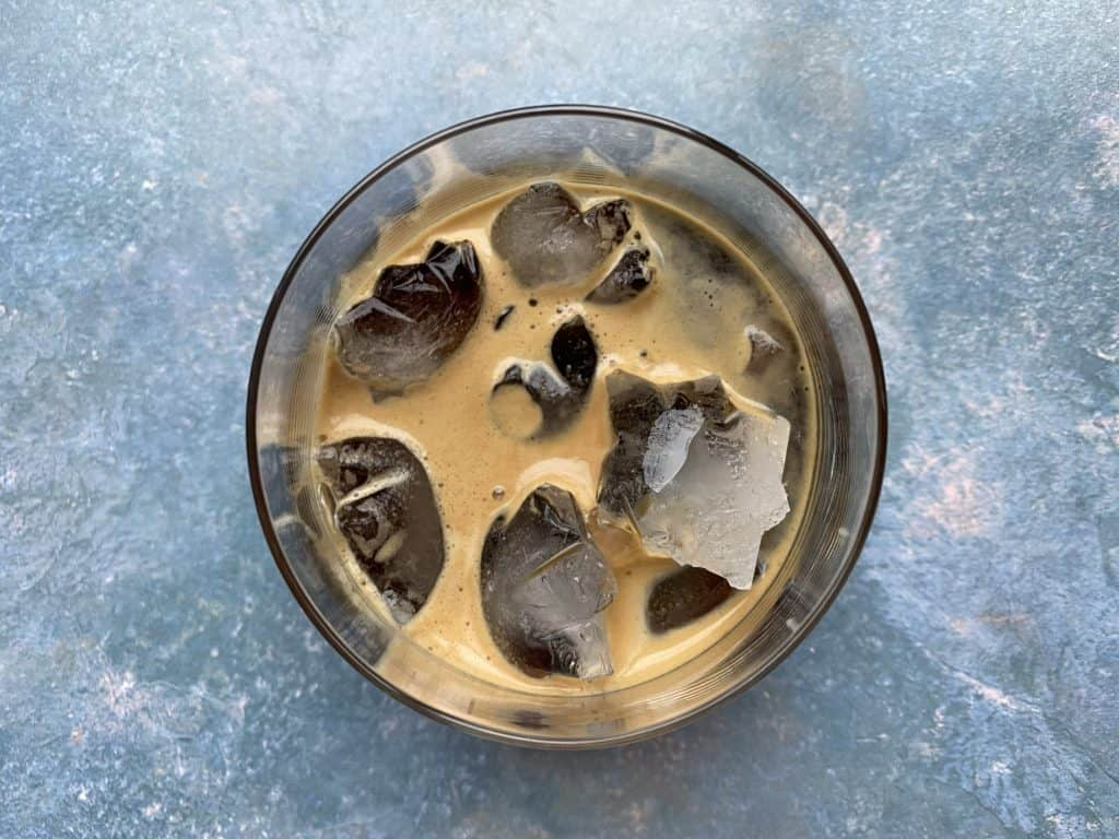 """""""Espresso and ice cubes combined in a glass cup"""""""