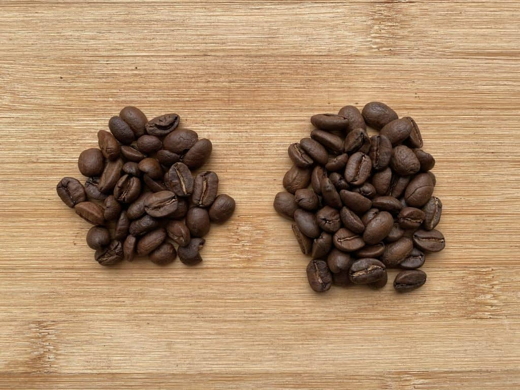 """Decaf coffee and regular coffee beans on a wooden plate for comparison."""""""
