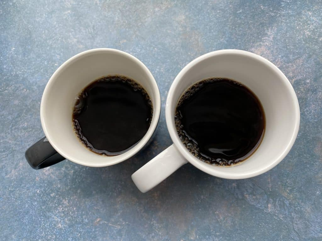 """""""Decaf coffee and regular coffee comparison in two mugs."""""""