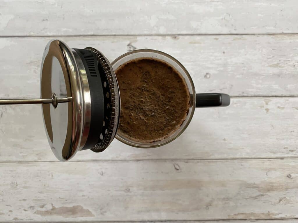 Filtering the French press cold brew by adding the plunger.