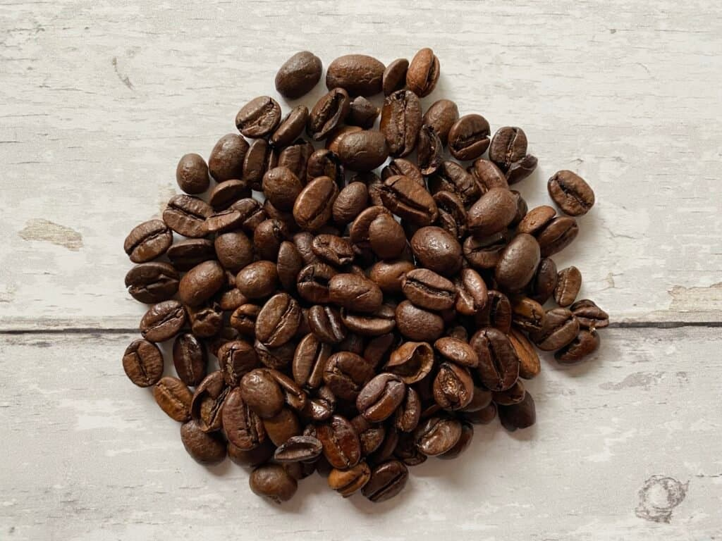 Dark roasted coffee beans used to brew espresso in a French press.